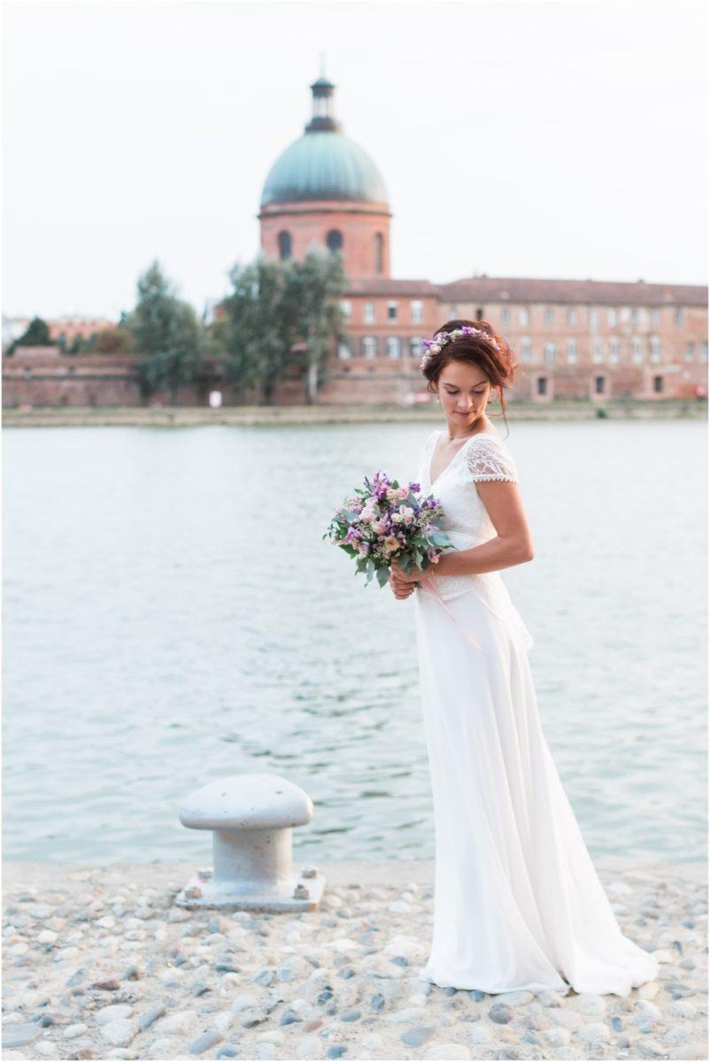 photo de mariée devant la garonne avec un bouquet dans les main