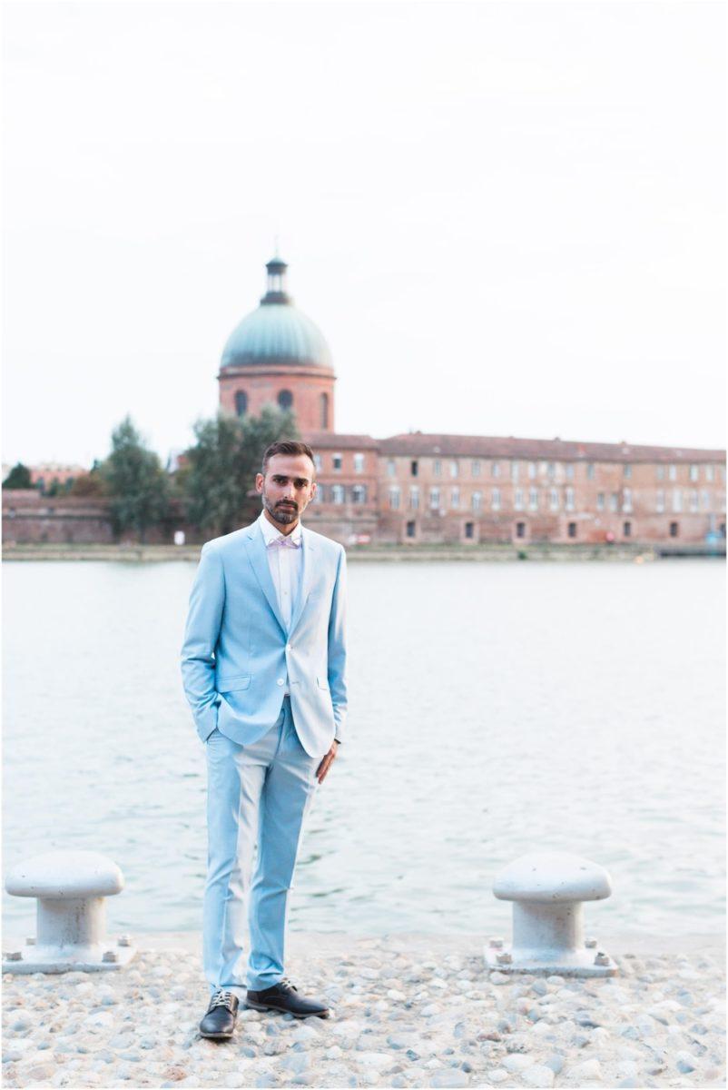 marié qui pose au bord de la Garonne dans un costume bleu