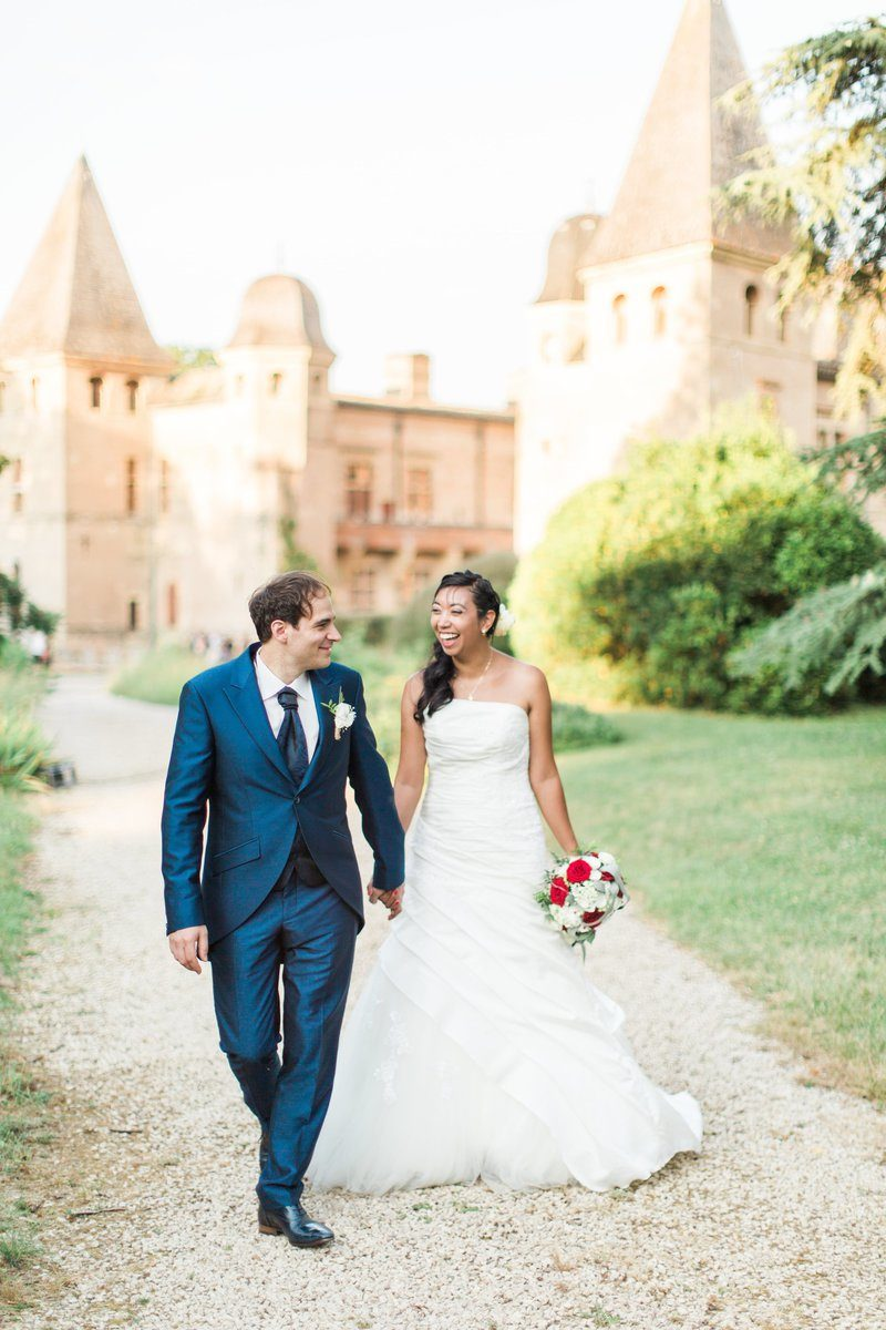 un couple de mariés marche devant le château de caumont