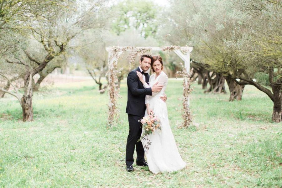 couple de marié qui se prend dans les bras dans un champs