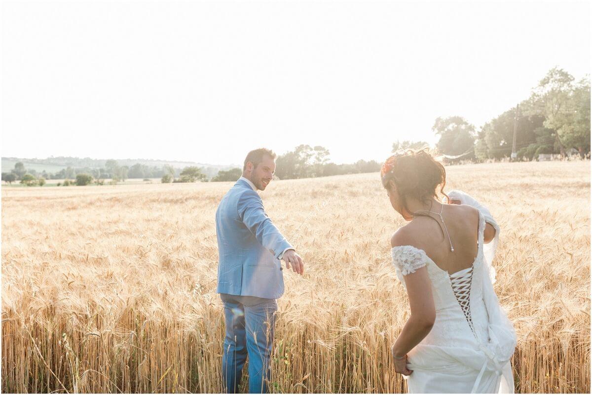 mariés qui marchent dans un champs de blés