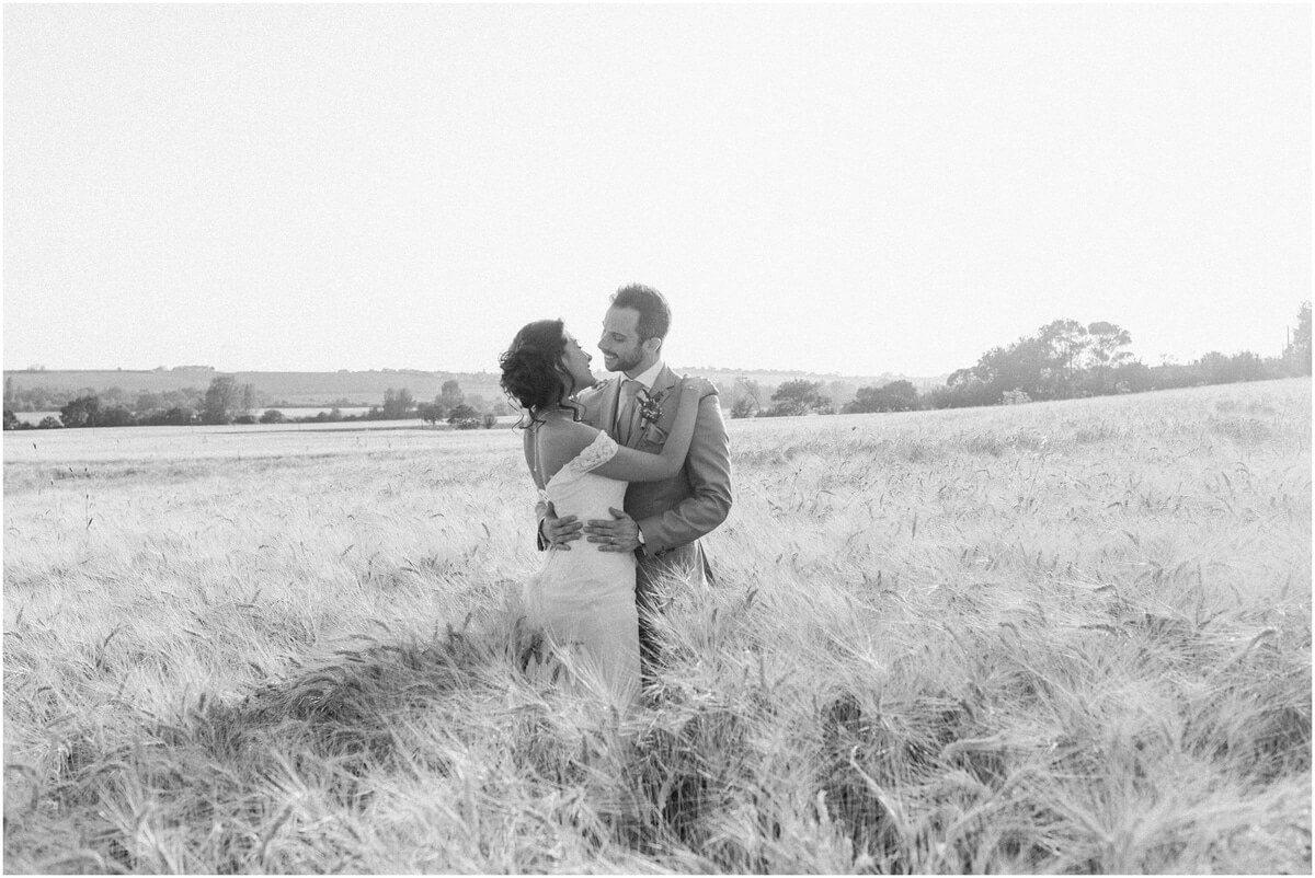 photo noir et blanc mariés qui marchent dans un champs de blés