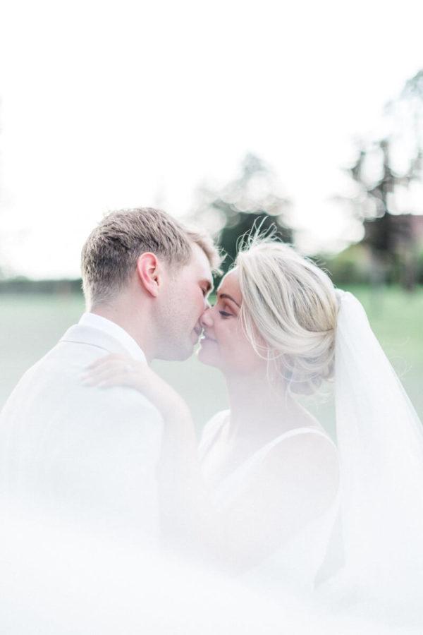 portrait de couple de mariés dans le jardin du chateau de varennes qui s'embrassent