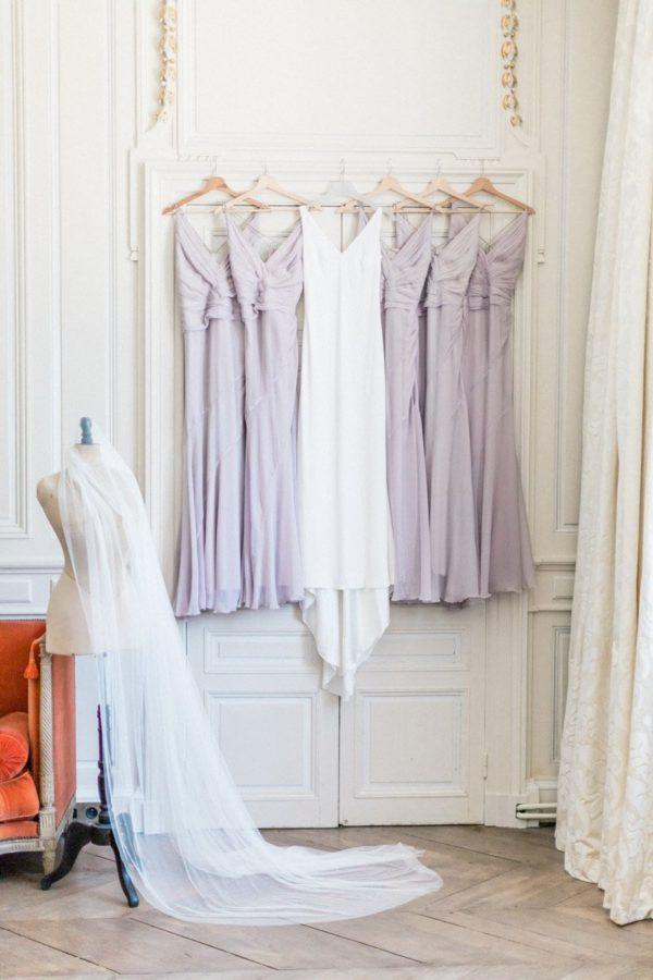 robe de mariée et robe de demoiselle d'honneur suspendues sur la porte de la chambre dans le château de varennes