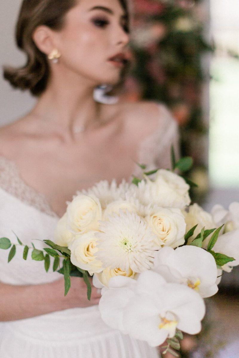 mariée debout avec son bouquet de fleur au chateau le buisson garembourg