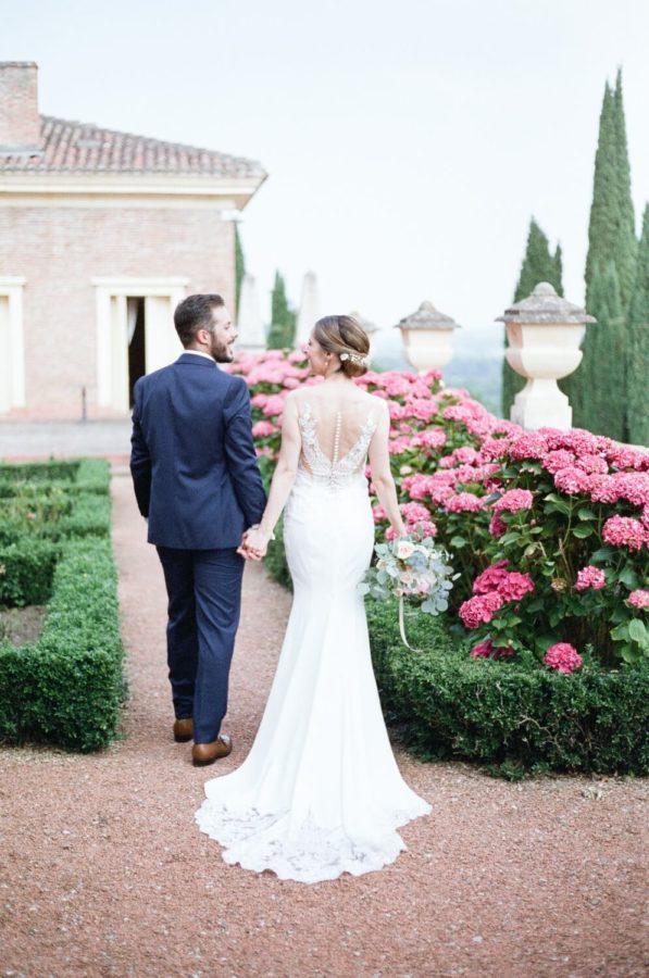 couple de mariés qui se prennent par la main et qui marche au chateau de roques